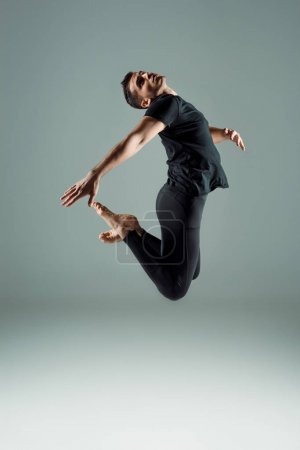 Photo for Handsome dancer in black leggings and t-shirt dancing contemporary on dark background - Royalty Free Image