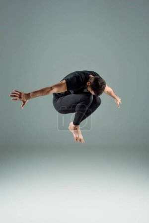 Photo for Dancer in black leggings and t-shirt dancing contemporary on dark background - Royalty Free Image