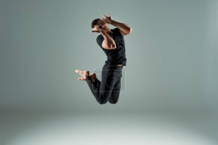 Photo for Handsome dancer with closed eyes in black leggings and t-shirt dancing contemporary on dark background - Royalty Free Image