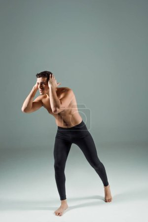 Photo for Handsome dancer in black leggings dancing contemporary on dark background - Royalty Free Image