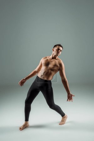 Photo for Handsome dancer with closed eyes in black leggings dancing contemporary on dark background - Royalty Free Image