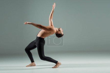 Photo pour Vue latérale d'une belle danseuse aux yeux fermés aux jambières noires dansant contemporain sur fond sombre - image libre de droit