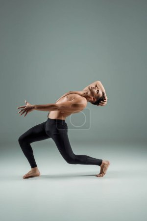 Photo for Side view of handsome dancer with closed eyes in black leggings dancing contemporary on dark background - Royalty Free Image