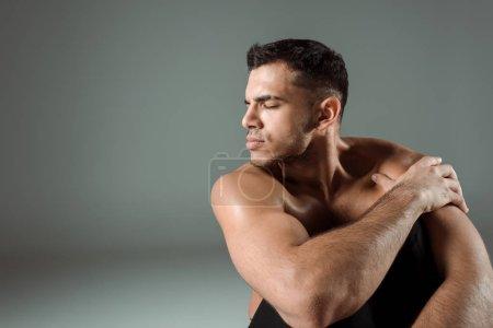 Foto de Bailarín guapo con los ojos cerrados bailando contemporáneo sobre fondo gris. - Imagen libre de derechos