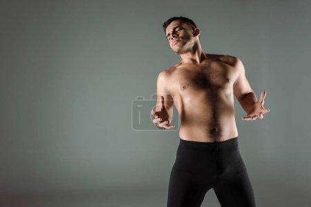 Photo pour Belle danseuse aux yeux fermés aux jambières noires danse contemporaine isolée sur grise - image libre de droit