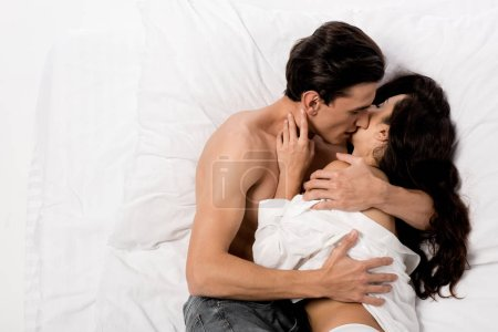 Photo for Top view of seductive couple kissing and lying on white bed - Royalty Free Image