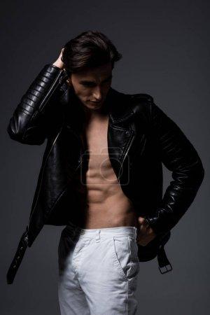 Photo pour Homme sexy torse nu en veste en cuir noir, isolé sur gris - image libre de droit