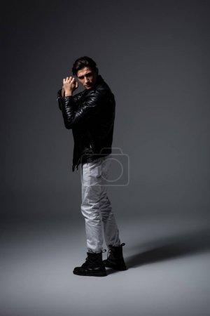 Photo pour Jeune homme en jean blanc et veste de cuir noir, sur gris - image libre de droit
