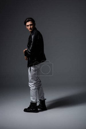 Photo for Handsome man in white jeans and black leather jacket, on grey - Royalty Free Image