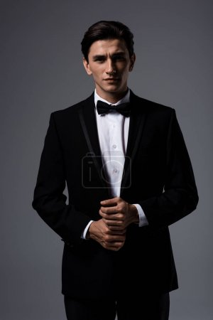 handsome young man in suit and tie bow, isolated on grey