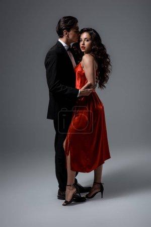 Photo pour Jeune couple romantique en costume et robe de soie rouge blottie sur gris - image libre de droit