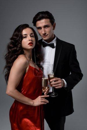 Photo pour Couple de fête romantique tenant des verres de champagne, isolé sur gris - image libre de droit