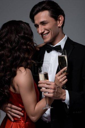 Photo pour Heureux couple festif tenant des verres de champagne et se regardant, isolé sur gris - image libre de droit