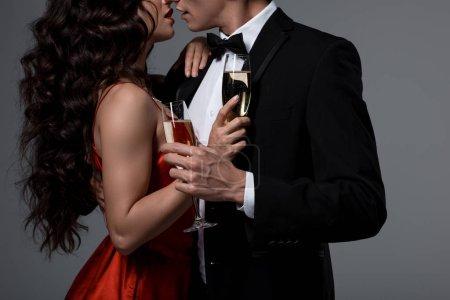 Photo pour Vue en coupe d'un couple serrant et tenant des lunettes de champagne, isolé sur gris - image libre de droit