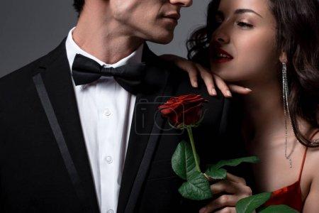 Photo pour Couple romantique tenant une rose rouge isolée sur fond gris - image libre de droit