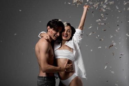 Photo pour Couple joyeux étreignant et s'amusant isolé sur gris avec des plumes - image libre de droit