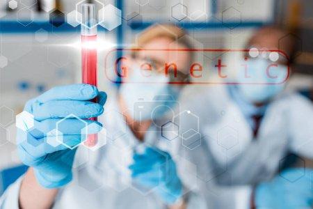 Photo pour Focalisation sélective de biologistes multiculturels examen d'un tube à essai avec illustration génétique - image libre de droit