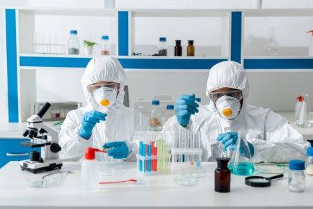 Photo pour Scientifiques multiculturels en combinaison de protection effectuant un test de dépistage en laboratoire - image libre de droit