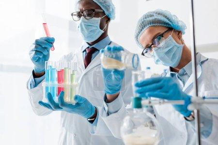 Photo pour L'orientation sélective de biologistes multiculturels effectuant des tests en laboratoire - image libre de droit