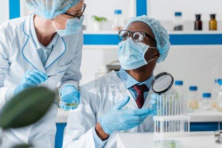 Photo pour Biologiste afro-américain en masque médical parlant avec un collègue en laboratoire - image libre de droit