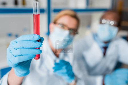 Photo pour Une approche sélective de biologistes multiculturels examinant des éprouvettes en laboratoire - image libre de droit