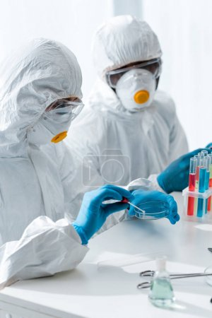 Photo for Multicultural scientists in protective suits doing dna test in lab - Royalty Free Image