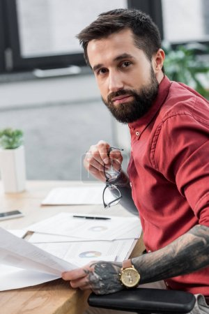 Photo for Handsome account manager sitting at table and holding glasses - Royalty Free Image