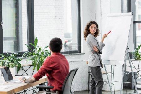 Photo pour Gestionnaire de comptes debout près du tableau à feuilles mobiles et parlant avec un collègue - image libre de droit