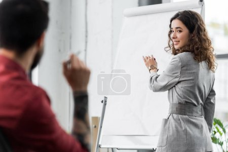 Photo for Selective focus of account manager standing near flipchart and talking with colleague - Royalty Free Image