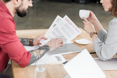 Photo pour Vue en coupe des directeurs de comptes qui s'occupent de la paperasse et de la tasse de retenue - image libre de droit