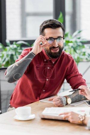Photo pour Souriant gestionnaire de compte dans des lunettes en regardant son collègue - image libre de droit