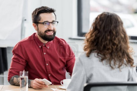 Photo for Selective focus of smiling account manager looking at colleague - Royalty Free Image