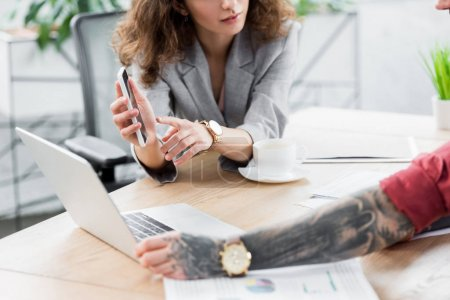 cropped view of account manager pointing with finger at smartphone and talking with colleague