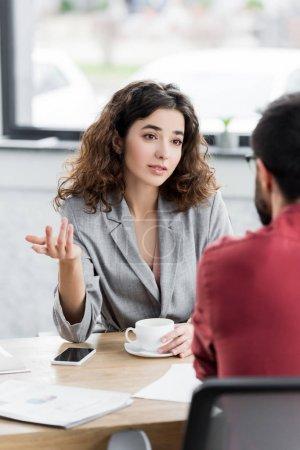 Photo pour Orientation sélective du gestionnaire de compte parlant avec un collègue et tenant la tasse - image libre de droit
