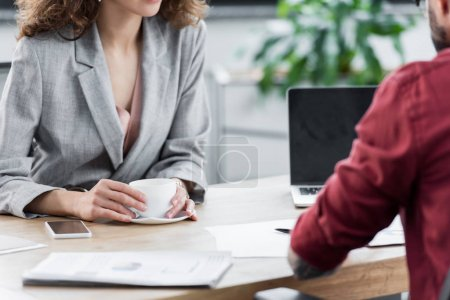 cropped view of account managers sitting at table in office