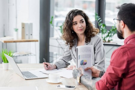 account manager sitting at table and talking with colleague