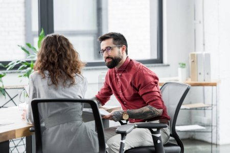 account managers talking and sitting at table in office