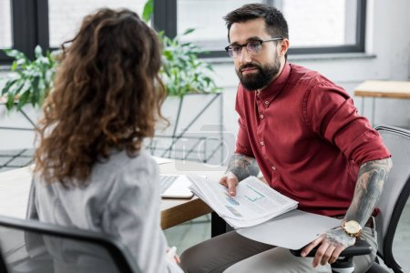 selective focus of account manager holding papers and talking with colleague