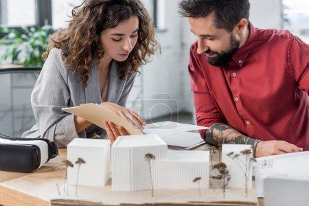 Photo pour Architectes de réalité virtuelle assis à table et faire de la paperasserie - image libre de droit