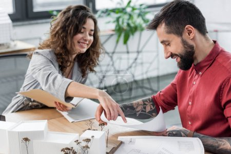 Photo pour Des architectes souriants de réalité virtuelle pointant du doigt des plans et faisant de la paperasserie - image libre de droit