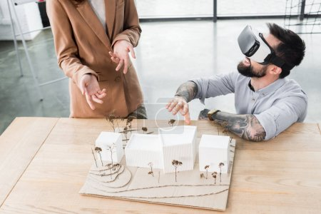 Photo for Virtual reality architect in virtual reality headset talking with colleague - Royalty Free Image
