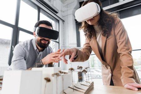 Virtual-Reality-Architekten in Virtual-Reality-Headsets zeigen mit dem Finger auf Modell eines Hauses