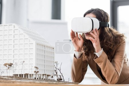 Photo for Virtual reality architect in virtual reality headset looking at model of house - Royalty Free Image