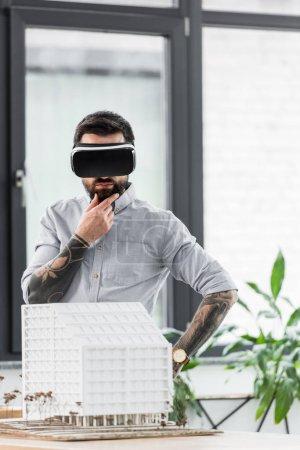 Photo pour Cher architecte de réalité virtuelle en réalité virtuelle casque regardant le modèle de maison - image libre de droit