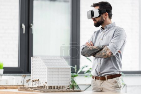 Photo for Virtual reality architect with crossed arms in virtual reality headset looking at model of house - Royalty Free Image
