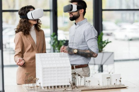 Photo for Virtual reality architects in virtual reality headsets talking in office - Royalty Free Image