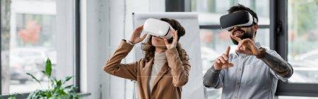 Foto de Foto panorámica de los arquitectos de realidad virtual sonrientes en los auriculares de realidad virtual apuntando con el dedo. - Imagen libre de derechos