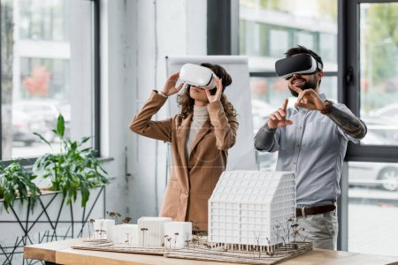 Photo for Smiling virtual reality architects in virtual reality headsets pointing with finger - Royalty Free Image