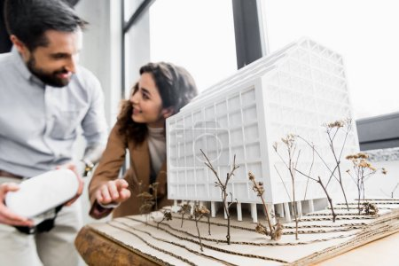 Photo for Selective focus of model of house and virtual reality architects talking on background - Royalty Free Image