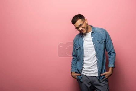 Photo pour Beau homme avec les mains dans les poches souriant à la caméra sur fond rose - image libre de droit